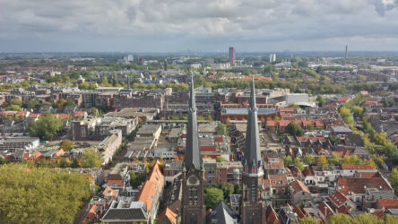 Looking over the Maria van Jessekerk over Delft. TU Delft (Delft University of Technology) is in the background, and Rotterdam is barely visible on the horizon