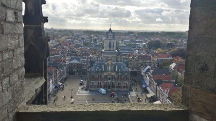 Delft's town hall, through the stonework of one of the lower balconies on the belltower of the Nieuwe Kerk