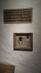 These holes were from the gun of Balthasar Gérard, who assassinated William of Orange at this spot in his house (now known as the Prinsenhof) on July 10, 1584. It was the first assassination where a handgun was used.